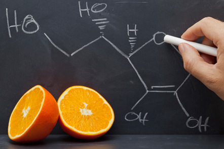 Half an orange with chemical structure written on chalkboard.