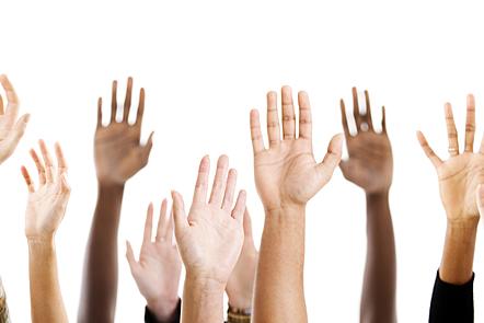 La imagen muestra muchas manos levantadas de diversas personas de diferente color.