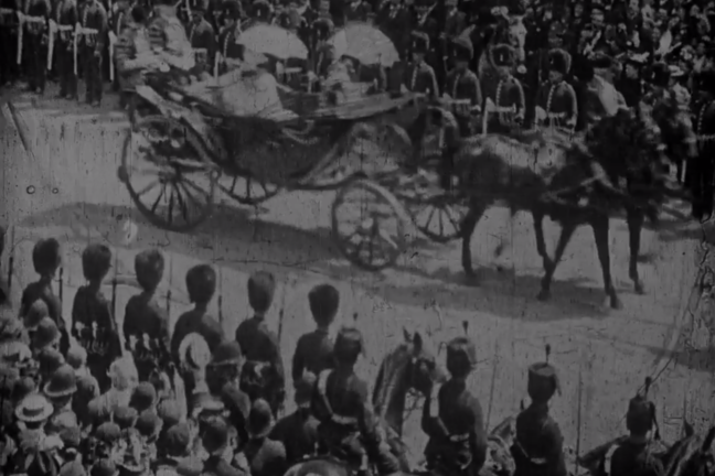 A black and white image of Queen Victoria's Diamond Jubilee. She's travelling through the crown in a carriage being pulled by horses.
