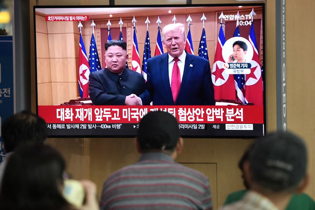 People watch a television news showing a file footage of a meeting between US President Donald Trump and North Korean leader Kim Jong Un which held at the truce village of Panmunjom, at a railway station in Seoul.