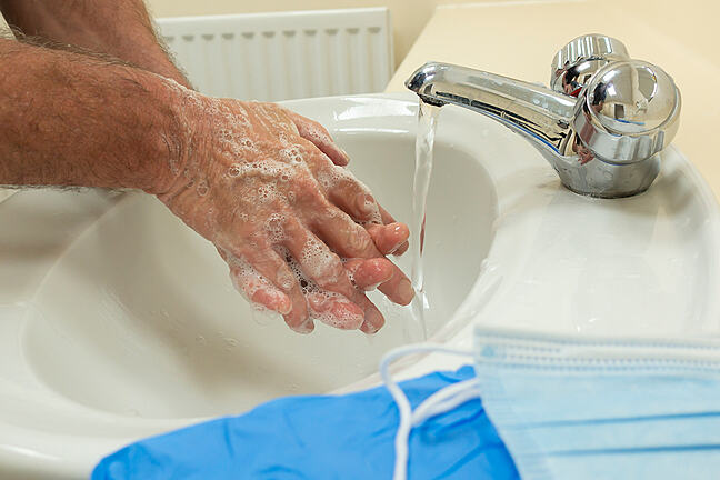 Man washing hands in preparation of putting on PPE