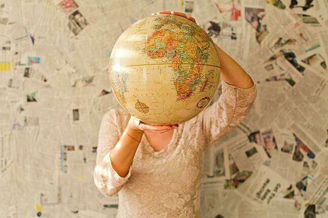 Two hands holding a large globe in front of the face of a person: torso and legs visible on a background of newspaper clippings.