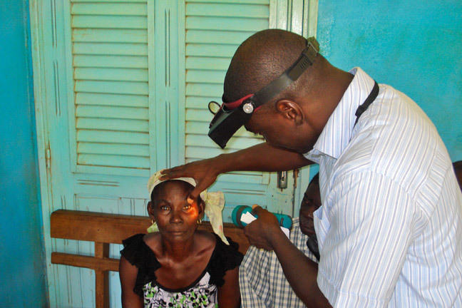 An eye care worker examines a female patient's eyes.
