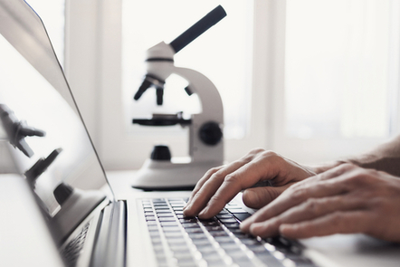 A person types on a laptop keyboard. There is a microscope next to the laptop.
