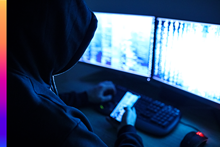Hacker at a computer and holding a cellphone while breaking into the system