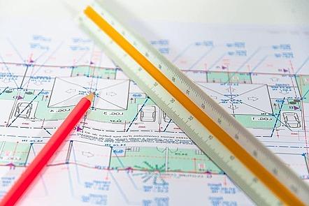 La imagen muestra una regla de escala triangular y un lápiz, ambos están encima de un plano