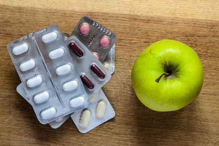 Photo of an apple and pharmaceuticals.