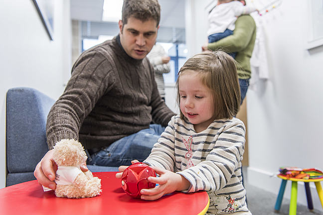 A child and her father playing a game