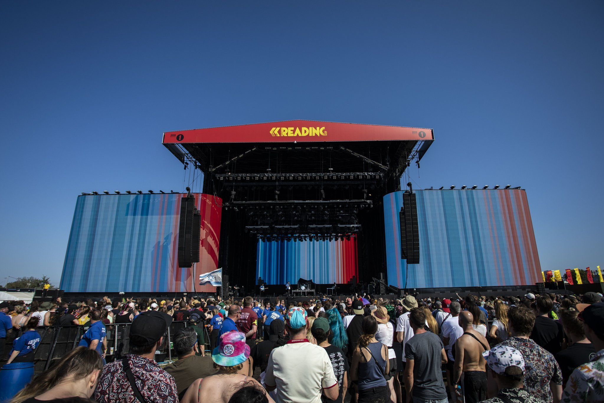 The front of a large festival stage that has 3 large screens, 1 on each side of the stage and 1 at the back. The screens show how the average global temperatures have risen since 1850, in the form of blue stripes for cooler years and red for hotter years.