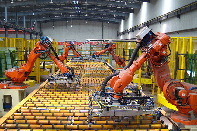 Industrial robots working with glass: Industrial warehouse, 4 orange robot 'arms' working at a large platform with yellow rollers.
