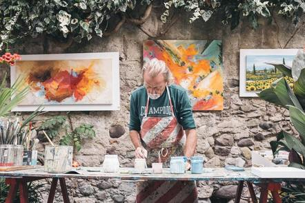 An older man crafting with paint and paper.