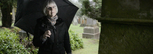 Genealogy: a lady looks at a tombstone in a graveyard while researching her family tree