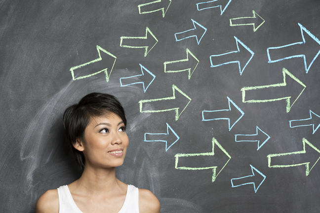Woman standing in front of a chalkboard with arrows pointing in the forward direction