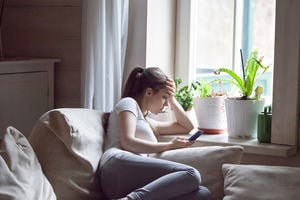 A teenage girl sits by the window, looking at her mobile phone, head in her hand