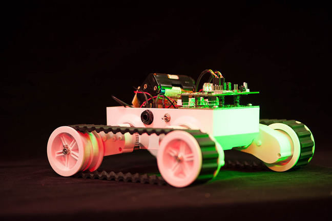 Rover robot consisting of a platform supporting circuit boards, motors and power packs, with 4 wheels connected by 'caterpillar' tracks.