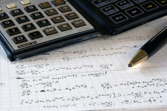 Calculator pen and paper showing scientific calculations