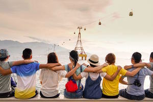 A group of people, facing away from us, siting on a quayside, looking out over a bay, with their arms interlinked