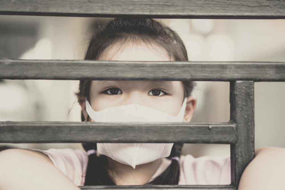 Girl wearing mask looking out of the window