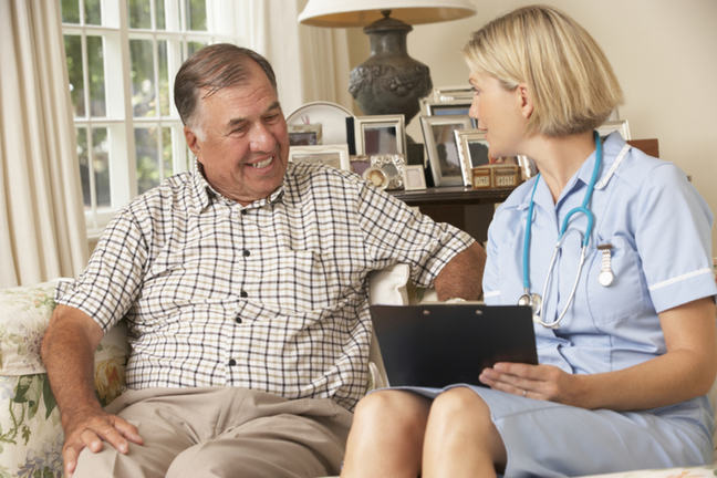 A nurse sitting talking to a man in a sitting room with a clipboard in her hand.