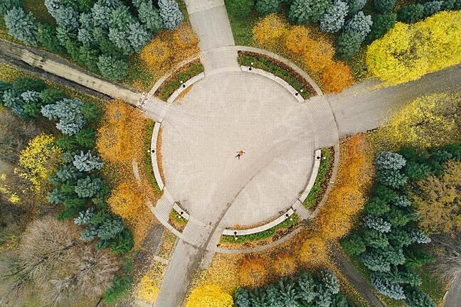 birds-eye view of  an empty road roundabout surrounded by trees