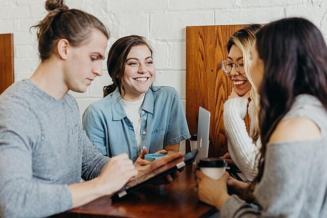 Four young people chatting in a cafe