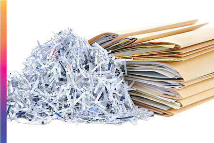 Photographic image of a stack of files with shredded paper next to it