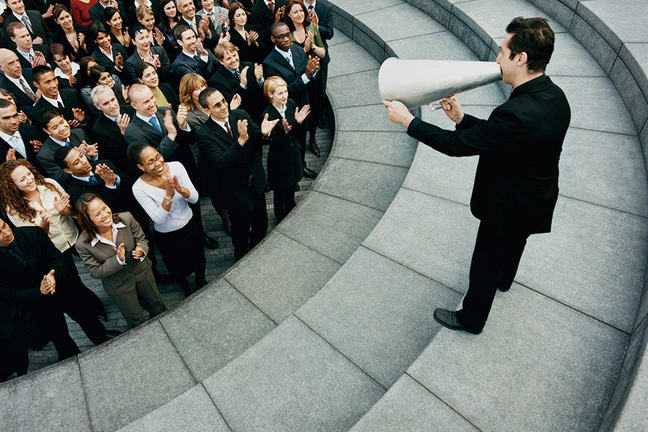 Businessman speaking to the masses in an amphitheatre using a megaphone.