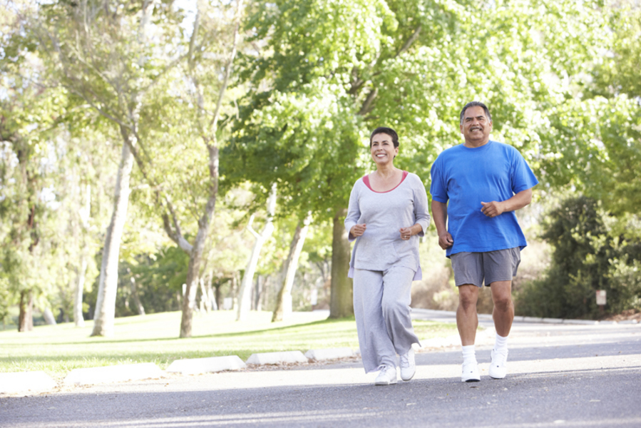 A man and woman running in a leafy park.