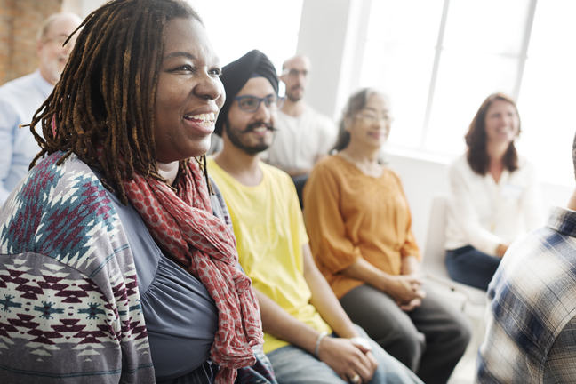 Smiling people sitting in a support group