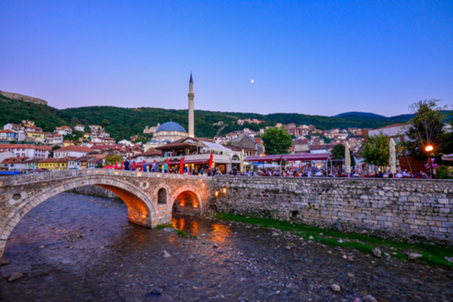 Image of a Kosovan village with a bridge, river and homes.