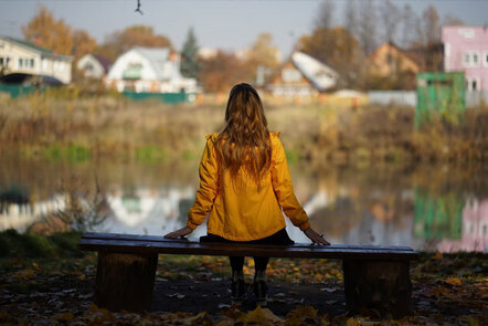 Image shows a person sat on a bench looking out at a village landscape across a lake.