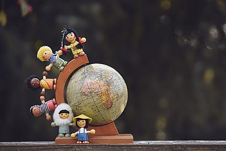 La imagen muestra seis pequeños juguetes, cada uno de ellos representa a diferentes niños y niñas. Están alrededor de un globo terráqueo sobre un trozo de madera. Todos sonríen y sus manos, formando un semicírculo, los conectan.