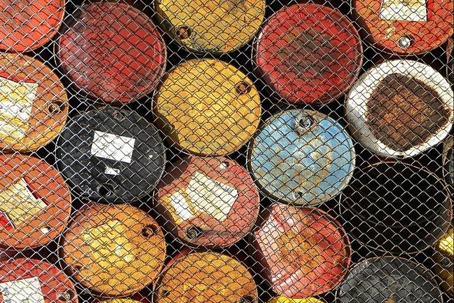 Oil barrels stacked behind wire fence