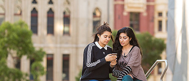 two CSU students looking at a phone on campus steps