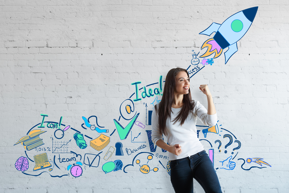 Young woman stands in front of a white wall illustrated with innovative ideas