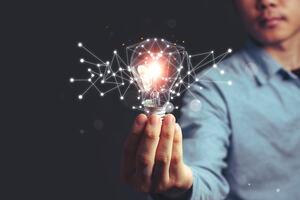 A man holds a lit lightbulb