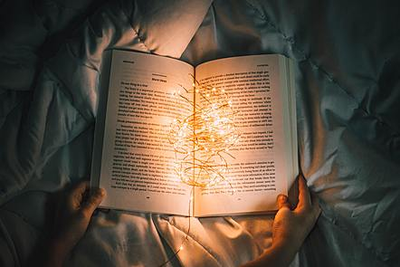 An open book held by a pair of hands, containing fairy lights.