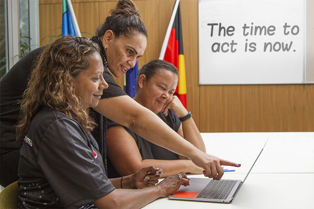 Three women looking at a laptop with text written on a whiteboard behind them: The time to act is now