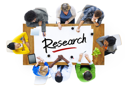 Group of people around a large piece of paper with the word research written on it