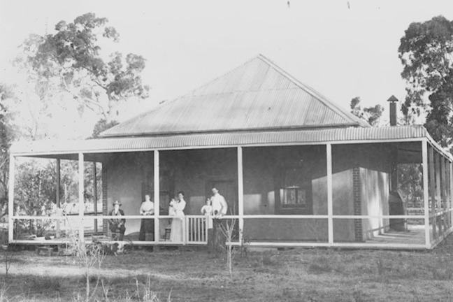 Historical photo of family standing on their front porch