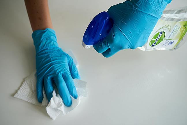 hands with gloves spraying surface and wiping with paper towel