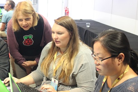 Two women working at computers, while another woman wearing a Raspberry Pi t-shirt assists them