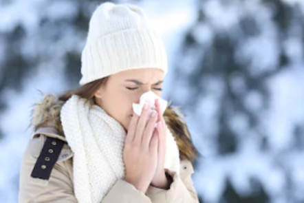 Lady outside in the cold sneezing into a tissue (IMAGE:©Shutterstock)
