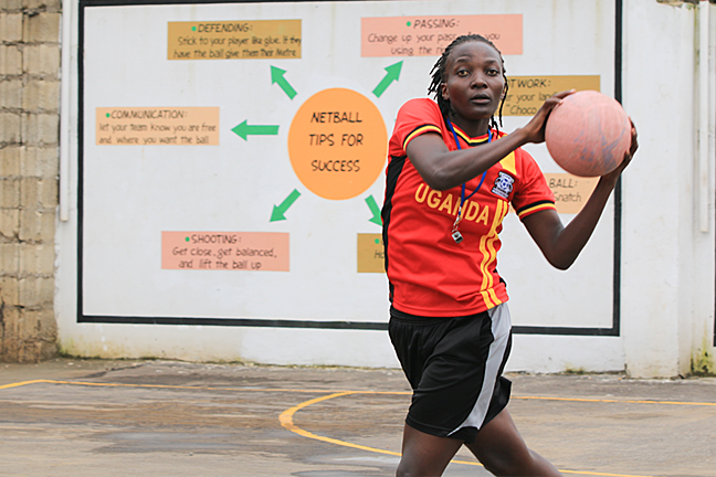 Female netball player wearing a Uganda t-shirt  in front of a sign that says tips for success
