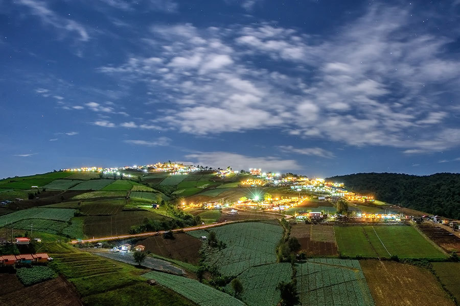 Village paddocks night scene with houses on hill