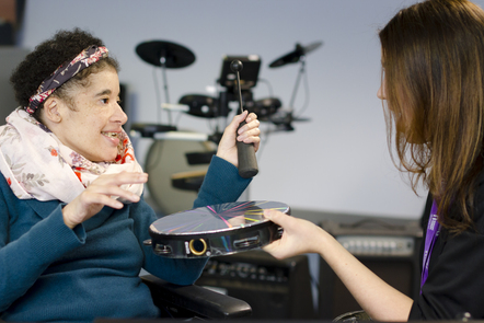 A woman is facing a female music therapist and using a stick to bang on a drum