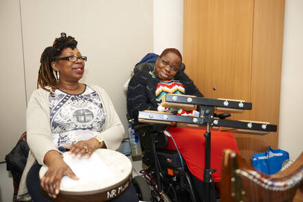 Two women are in a music session, one is playing a tambourine, the other is in a wheelchair smiling
