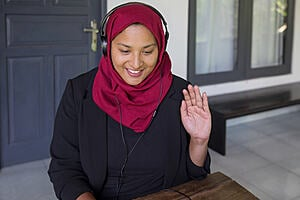 A lady with a headset on waving at a laptop