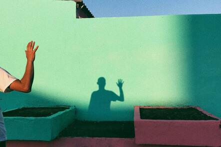 Shadow of a person waving on a green wall.