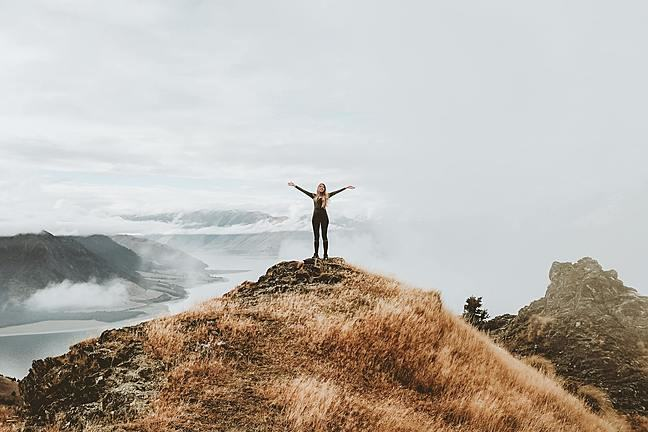 Lady standing on top of a hill reaching for the sky
